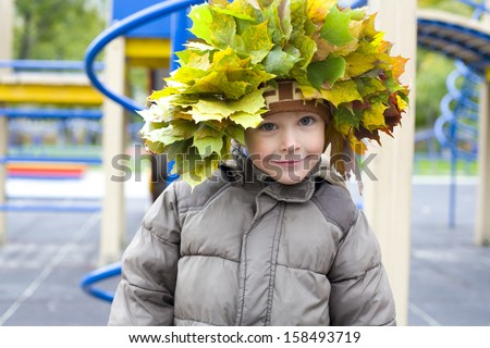 Portrait of beautiful four-year-old boy in a wreath from autumn leaves - stock photo