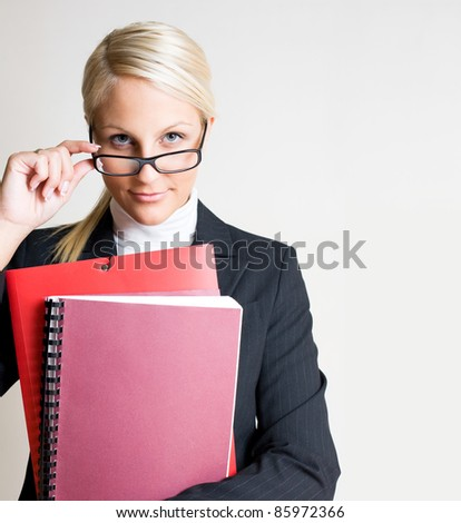 Portrait of beautiful friendly smiling businesswoman peeking over her glasses. - stock photo