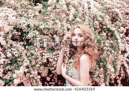 Portrait of beautiful girl against flowers.  - stock photo