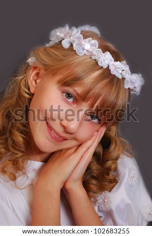 portrait of beautiful girl going to the first holy communion and posing in studio against dark background - stock photo