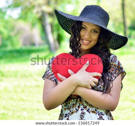 Portrait of beautiful girl holding big red heart - stock photo