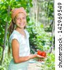 Portrait of beautiful girl holding tomatoes in green garden - stock photo
