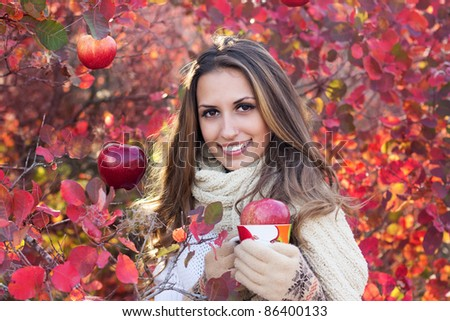portrait of beautiful girl in autumn leaves. With an cup in hand. - stock photo