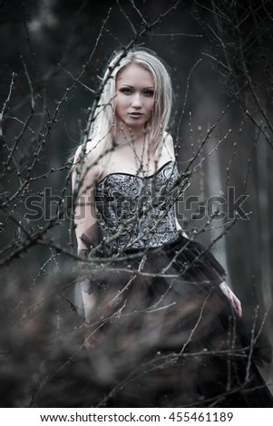 Portrait of beautiful girl in black dress in nature
