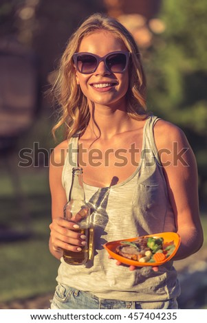 Portrait of beautiful girl in casual clothes and sun glasses holding bottle of beverage and food, looking at camera and smiling while resting outdoors - stock photo