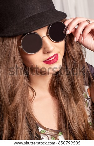 Portrait of beautiful girl in glasses and bowler-hat. Girl with red lips.