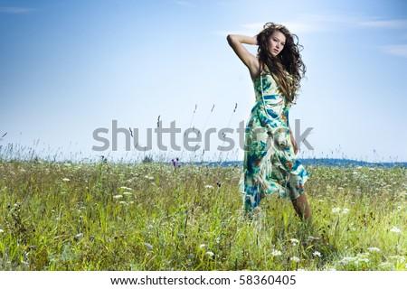 Portrait of beautiful girl in green field - stock photo