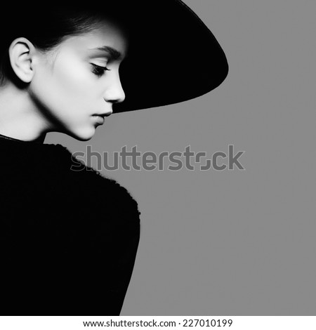 Portrait of beautiful girl in hat in profile, posing in studio, black and white photography - stock photo