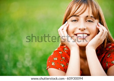 Portrait of beautiful girl in red dress which sits on green grass. - stock photo