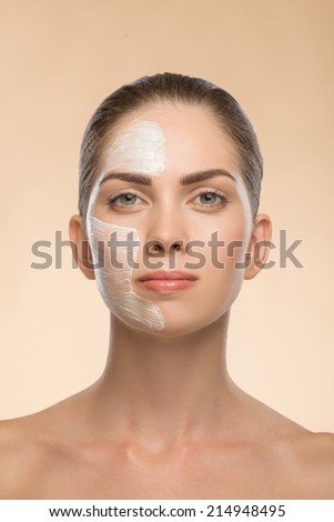 Portrait of beautiful girl in spa with cosmetic cream on her face with clean and  fresh skin isolated on beige background  with copy place - stock photo