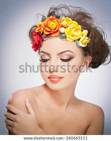 Portrait of beautiful girl in studio with red and yellow roses in her hair and naked shoulders. Sexy young woman with professional makeup and bright flowers. Creative hairstyle and makeup, studio shot - stock photo