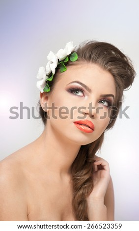 Portrait of beautiful girl in studio with white flowers arrangement in her hair and naked shoulders. Sexy young woman with professional makeup and flowers. Creative hairstyle and makeup, studio shot - stock photo
