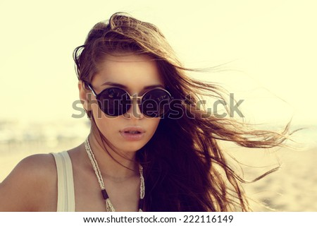 Portrait of beautiful girl in sunglasses at beach. Fashion style portrait - stock photo