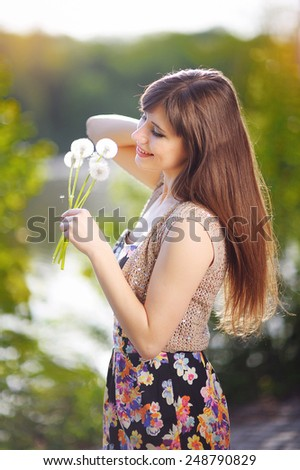 portrait of beautiful girl in the park holding dandelions. - stock photo