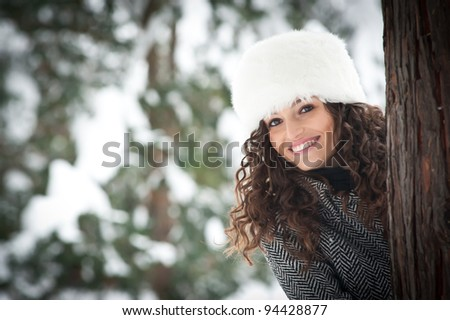 Portrait of beautiful girl in the snow hiding behind a tree. - stock photo