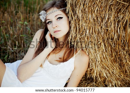 portrait of beautiful girl in white dress lying behind hay - stock photo