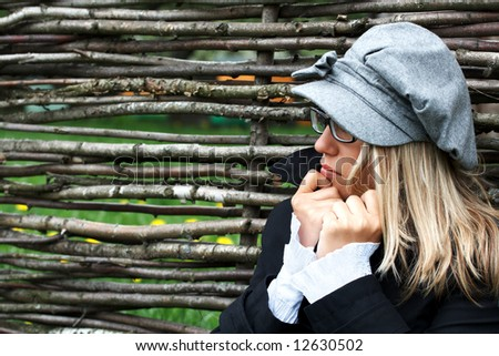 portrait of beautiful girl is feeling cold in the spring nature background and wooden fence; shallow DOF