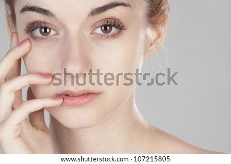 Portrait of beautiful girl of nineteen touching her hand to her face and looking at the camera close up