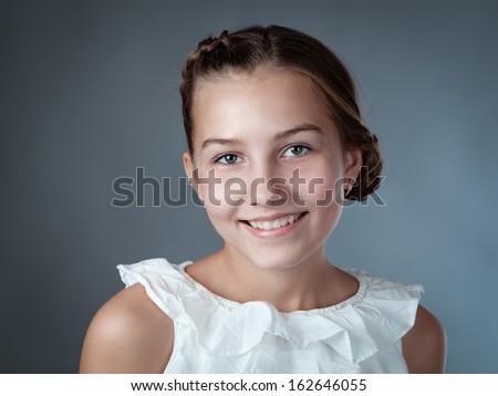 Portrait of beautiful girl on gray background, studio - stock photo