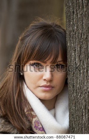 Portrait of beautiful girl outdoors leaning on a tree - stock photo
