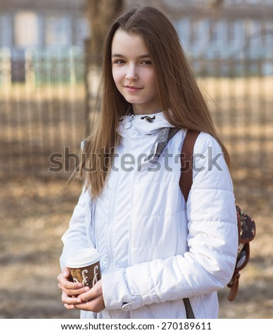 Portrait of beautiful girl schoolgirl brunette holding a cup of coffee in the fall or spring day, smiling happy. - stock photo