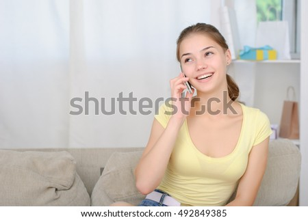 portrait of beautiful girl talking by phone in living room
