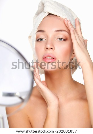 Portrait of beautiful girl touching her face with a towel on her head - stock photo