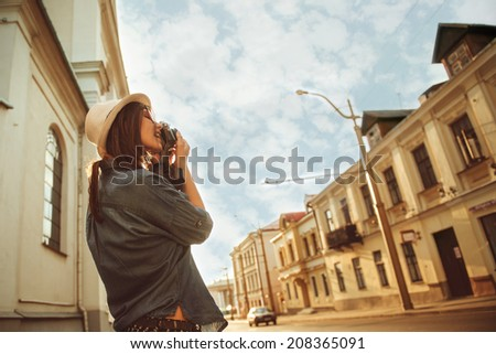 portrait of beautiful girl tourist photographing the old streets of the city - stock photo