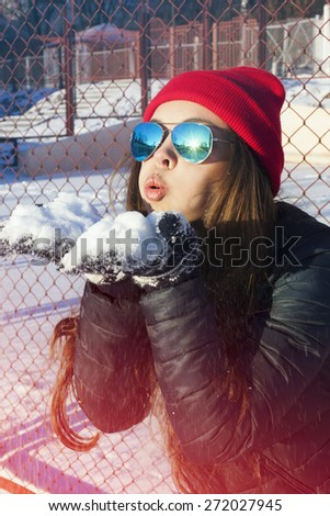 Portrait of beautiful girl wearing warm winter clothes ,red hat and sunglasses blowing snow in winter. Fashion. Lifestyle. Hipster. Woman have fun. - stock photo