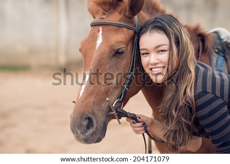 Portrait of beautiful girl with a chestnut pony - stock photo