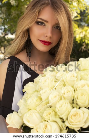 portrait of beautiful girl with blond hair holding a bouquet of white roses