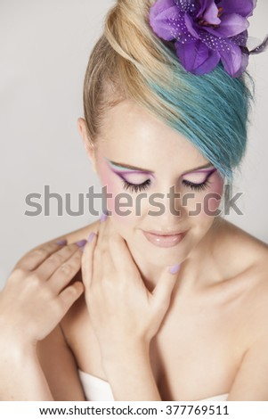 Portrait of beautiful girl with blonde and blue hair accessorized with a purple floral hair clip, wearing a strapless top with purple makeup and purple nail polish. - stock photo
