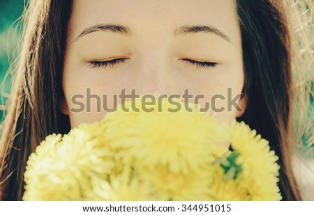 Portrait of beautiful girl with closed eyes with bouquet of yellow dandelions outdoor in summer, focus on eyes