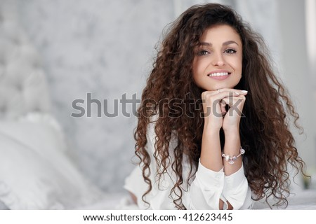 Portrait of beautiful girl with curly hair on the bed
