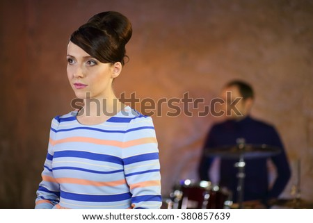 Portrait of beautiful girl with dark hair in a striped dress in front of a drummer - stock photo