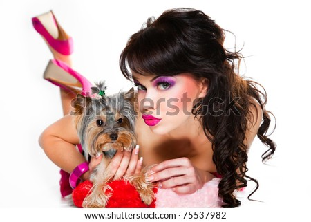 Portrait of beautiful girl with dark long curly hair and vibrant make-up wearing pink satiny ribbon holding small dog on white background - stock photo