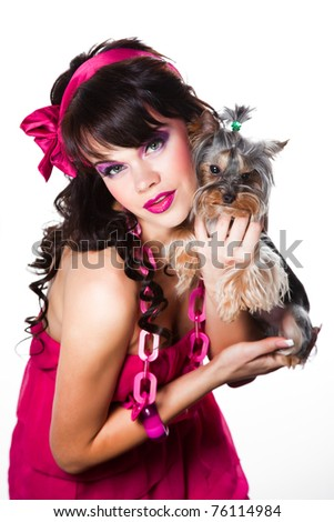 Portrait of beautiful girl with dark long curly hair and vibrant make up wearing pink satiny ribbon holding small small yorkshire terrier on white background - stock photo