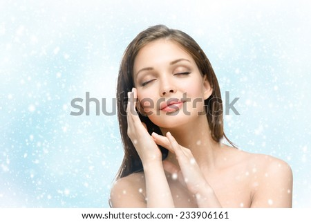 Portrait of beautiful girl with eyes closed touching face with hands, snowy background. Concept of beauty and youth