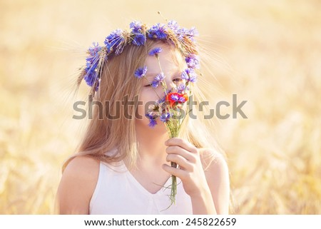 Portrait of beautiful girl with flowers crown smelling fields flowers outdoors. Concept of pollen allergy.  - stock photo