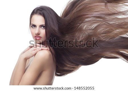 Portrait of beautiful girl with flying long dark hair over white background - stock photo