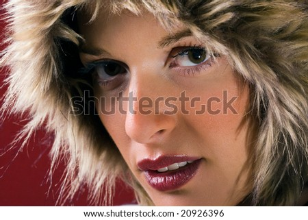 Portrait of beautiful girl with fur hood on red studio background