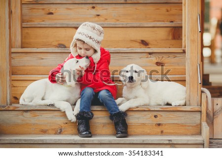 portrait of Beautiful girl with her two dogs labrador retriever. little child with two puppies of golden retriever sitting on stair steps. outdoor. cold weather. happy child - stock photo