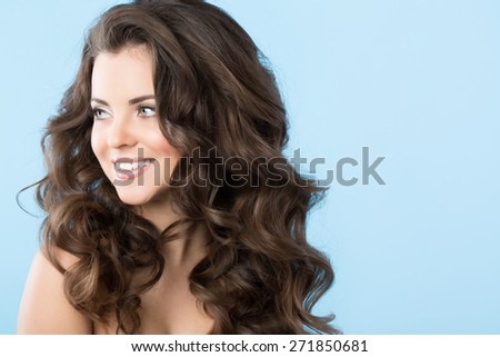 Portrait of beautiful girl with long hair waves on a blue background - stock photo