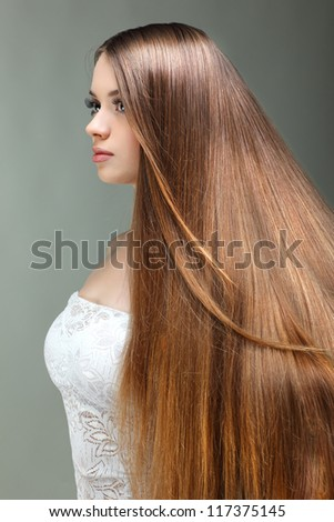 Portrait of beautiful girl with long hairs, on a grey background, emotions, cosmetics