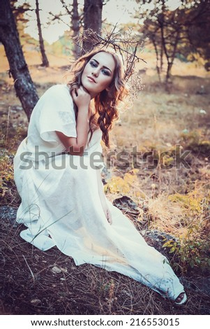 portrait of beautiful girl with magic eyes in wreath and dress in the forest outdoor. Bright witch, druid, shaman. book cover