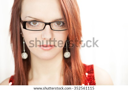 Portrait of beautiful girl with red hair wearing black thick framed glasses and spherical earings - stock photo