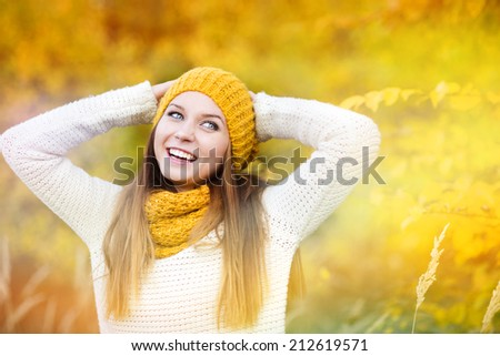 Portrait of beautiful girl with scarf and hat in yellow autumn nature - stock photo