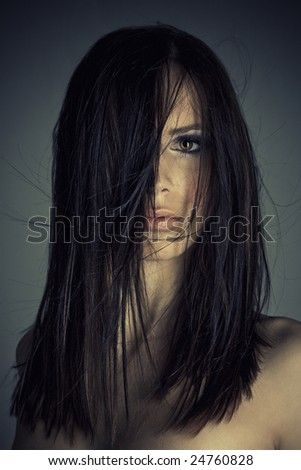 portrait of beautiful girl with strong look and blowing hair - stock photo