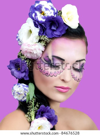 Portrait of beautiful girl with stylish makeup and violet flowers around her isolated against violet background