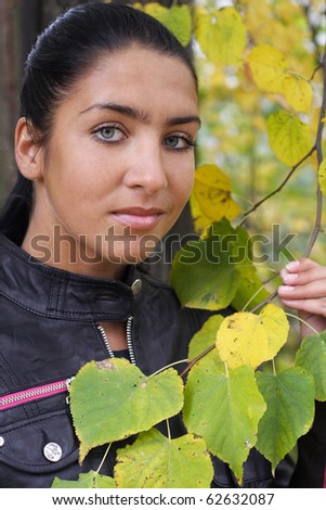 Portrait of Beautiful girl with yellow leaves outdoors. More images of this models you can find in my portfolio - stock photo